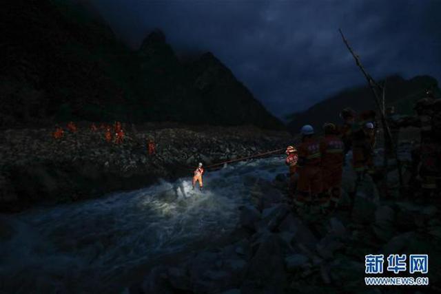 救援人员深夜溜绳索过河搜救